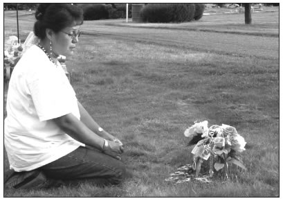 PAULINE MITCHELL SITTING AT THE GRAVE SITE OF HER SON